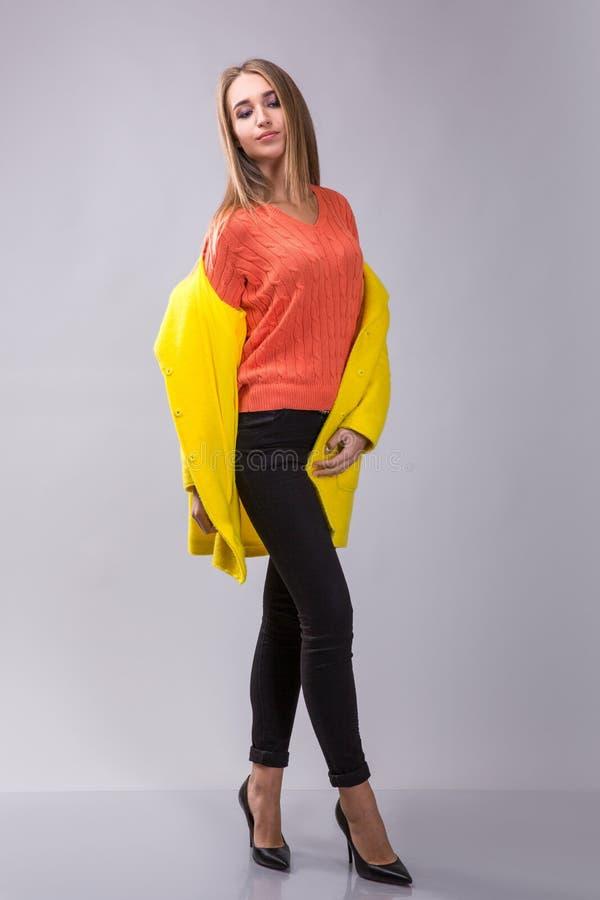 高雅女孩在灰色背景的演播室摆在 她穿黑裤子、橙色pulover和黄色外套 免版税库存照片