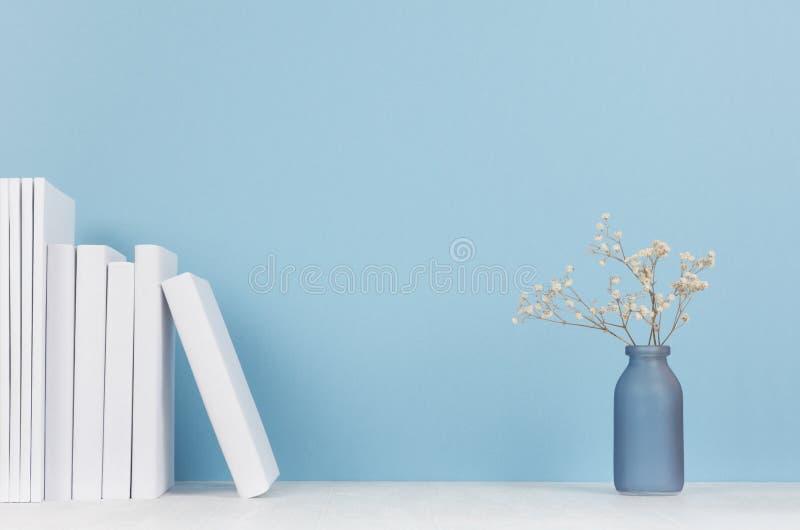 高雅家庭装饰-白皮书和小玻璃花瓶有干花的在柔光白色木桌和蓝色背景上 免版税图库摄影