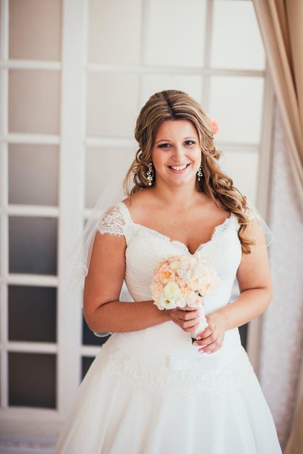 高雅逗人喜爱的新娘在背景屋子摆在 库存照片