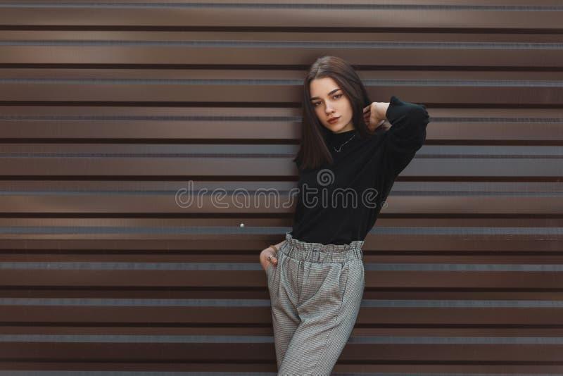 高雅黑毛线衣的时兴的美丽的年轻女人在摆在一个春日的时髦的黑方格花纹裤在城市 免版税图库摄影
