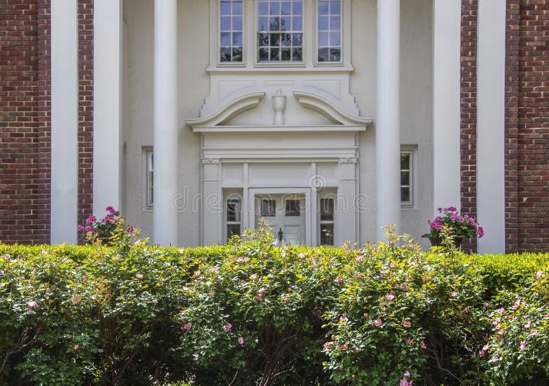 高雅-需要整理…在被遮蔽的被弄脏的华丽入口前面对高级砖和灰泥的Rosebush树篱 库存照片