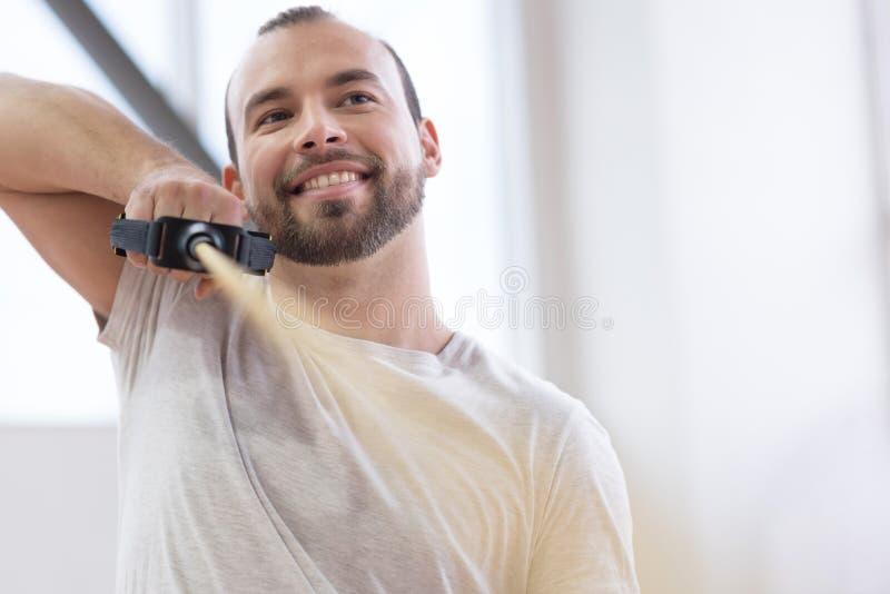 高兴年轻人妨碍了舒展在健身房的缆绳 库存图片