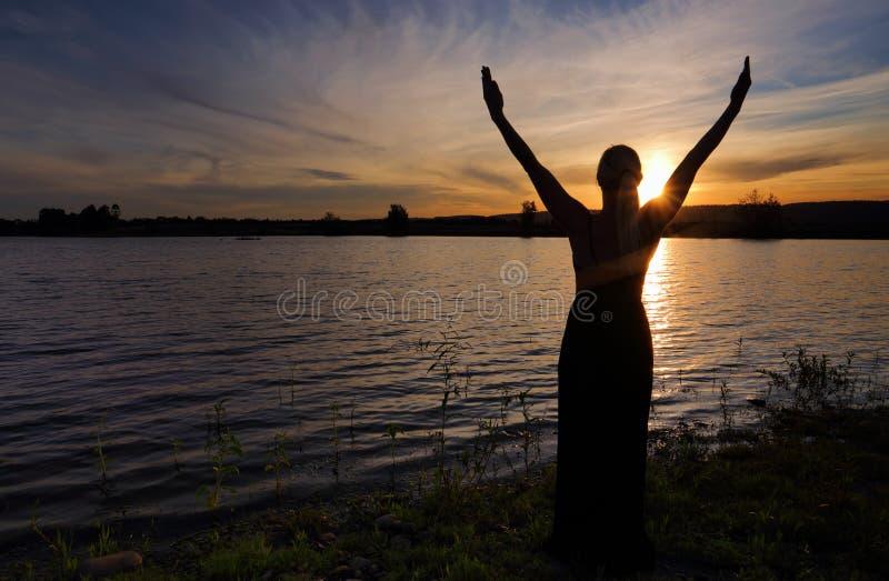 高兴人生的妇女反对日落天空 库存照片