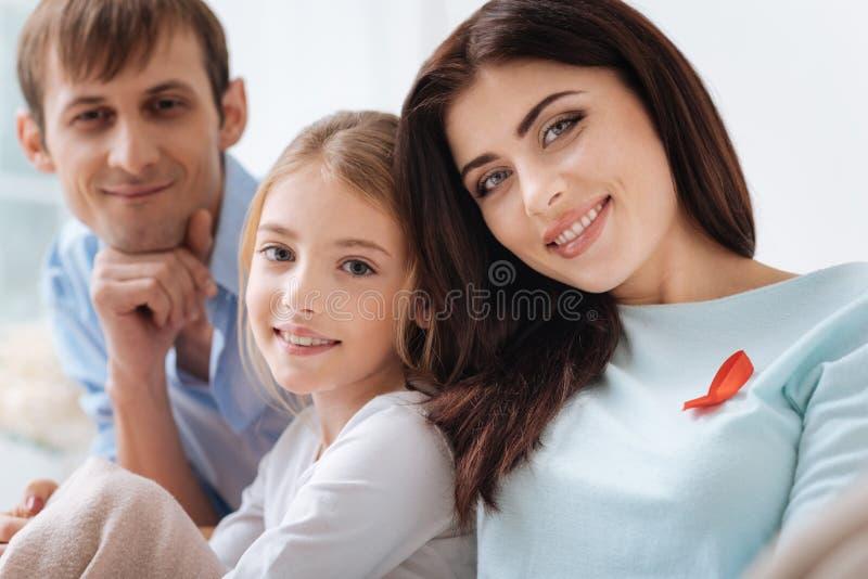 高兴宜人的妇女佩带的艾滋病红色丝带 免版税库存图片