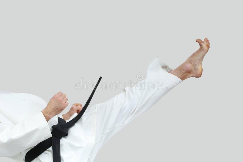 高直接的打击腿做着karategi的运动员 免版税库存照片