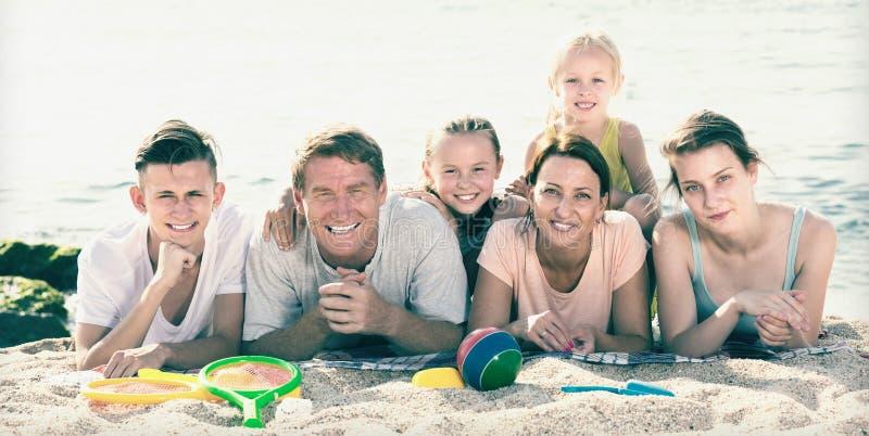 高兴的六口之家画象海滩的人 免版税库存图片