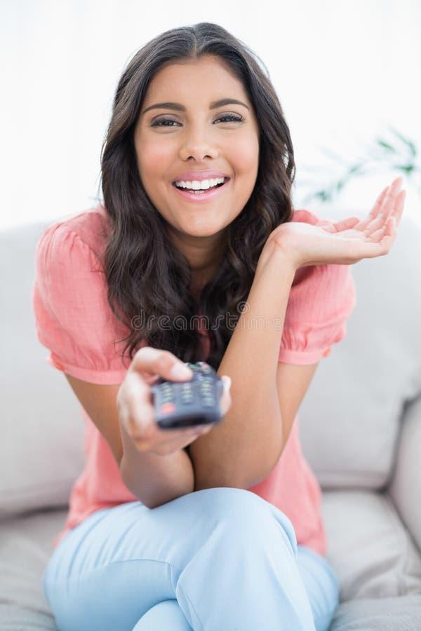 高兴的逗人喜爱的浅黑肤色的男人坐拿着遥控的长沙发 库存图片