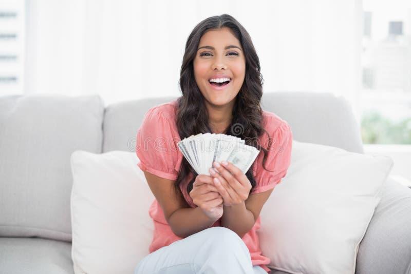 高兴的逗人喜爱的浅黑肤色的男人坐拿着金钱的长沙发 免版税图库摄影