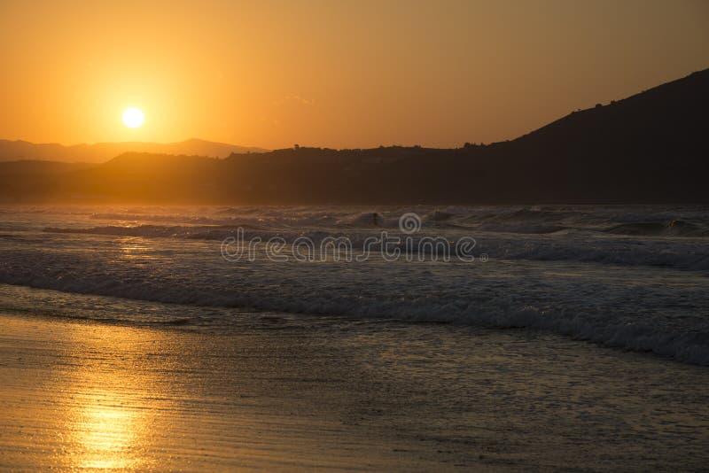 高JPG解决方法海运日落 在黄昏的晴朗的在背景的道路和小山 Georgioupolis海滩,克利特希腊 免版税库存图片