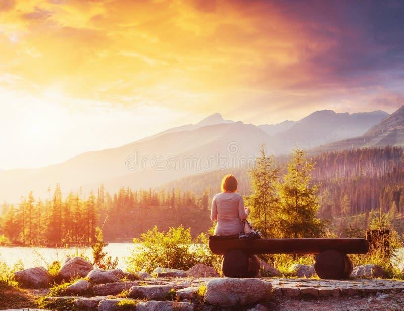 高Tatras山的,斯洛伐克,欧洲湖Strbske普莱索 女孩坐长凳并且调查童话天空 免版税库存图片