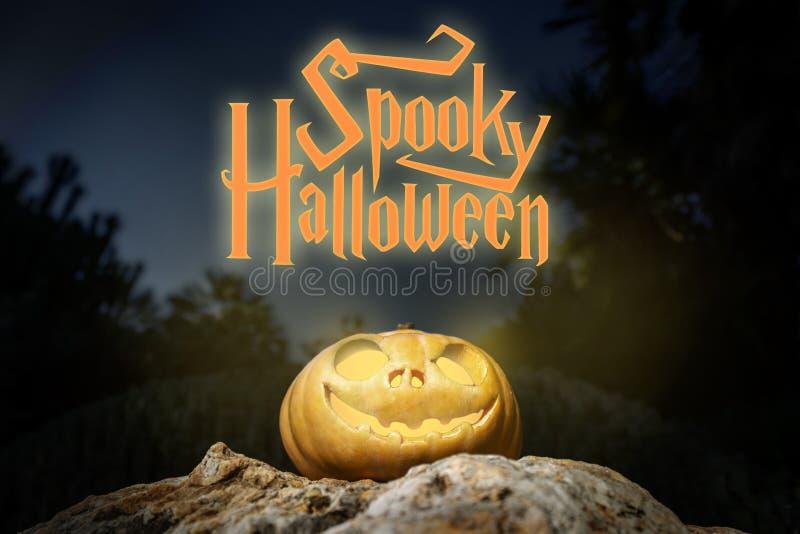 鬼的万圣夜温暖的霓虹南瓜在一个岩石在黑暗中 免版税图库摄影