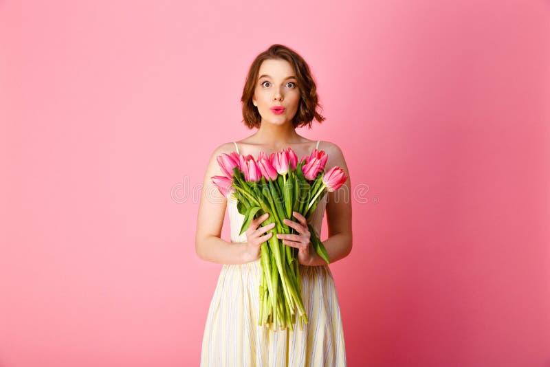 鬼脸妇女画象桃红色郁金香白色礼服藏品花束的  库存图片