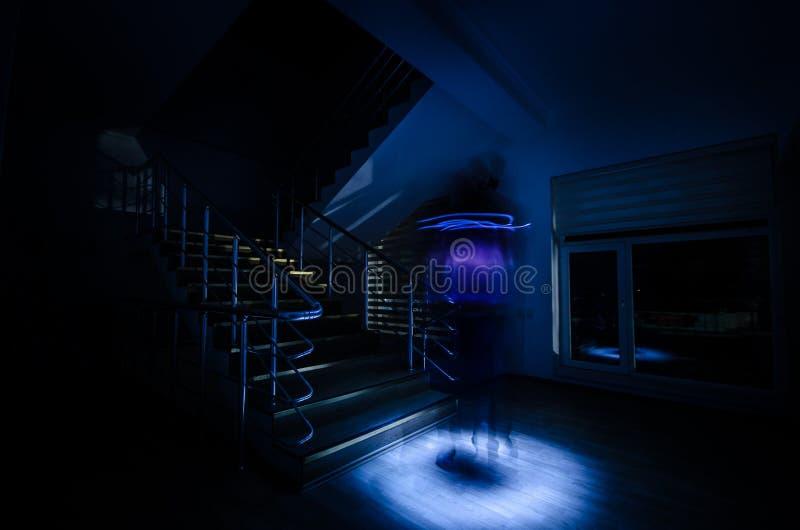 鬼魂在台阶的被困扰的议院,鬼魂人神奇剪影里有光的在台阶,可怕鬼魂鬼的llig恐怖场面  免版税图库摄影