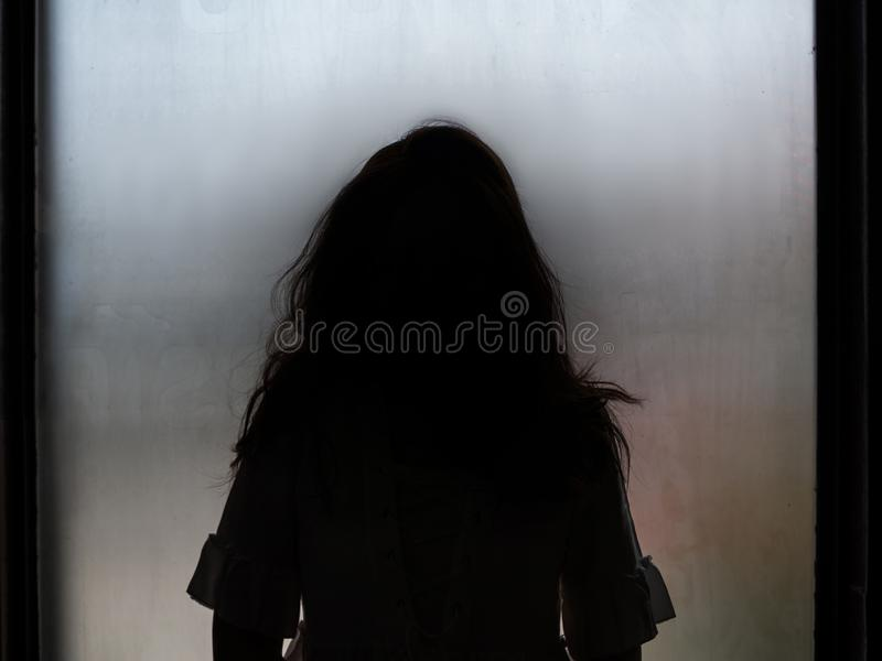 鬼魂站立在窗口前面的女孩剪影 免版税库存照片