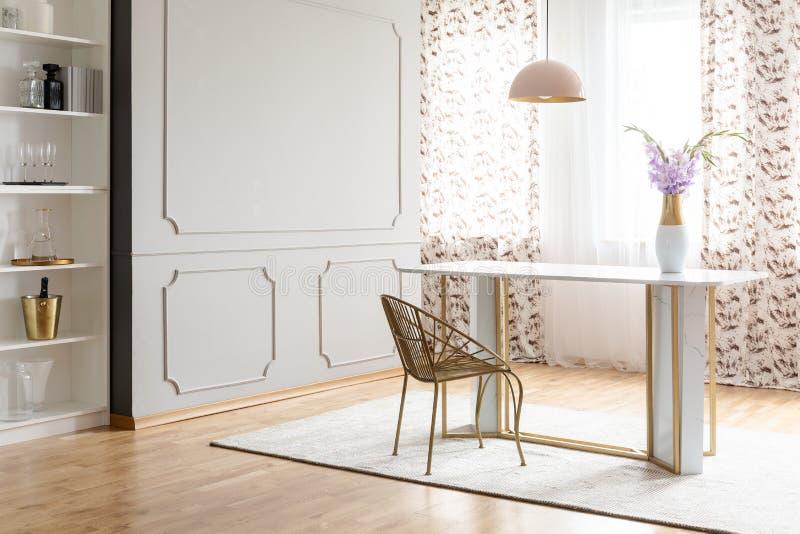 魅力与桌、椅子、花和空的墙壁的餐厅内部 安置您的绘画 库存照片