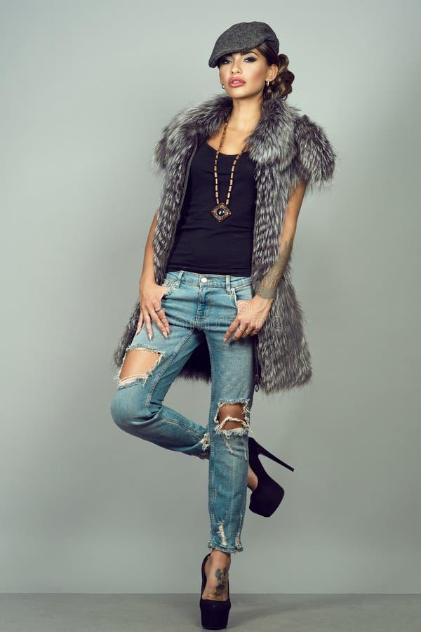 魅力与诱惑构成佩带的银狐夹克、被剥去的蓝色牛仔裤、高跟鞋和被锐化的盖帽的被刺字的模型 免版税库存照片