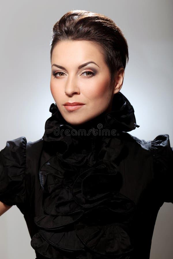 魅力和华美的浅黑肤色的男人有黑礼服的 免版税图库摄影