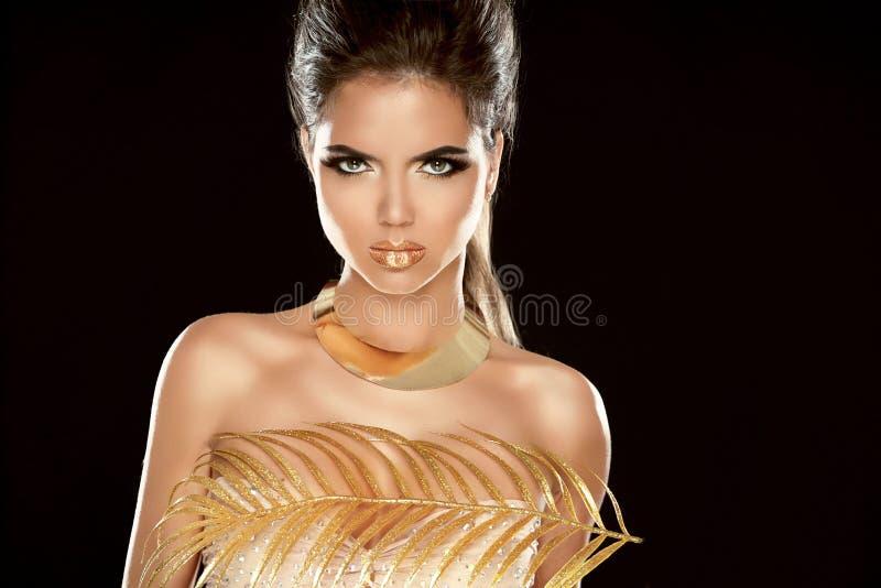 魅力时尚女孩与豪华金黄首饰的模型画象。 免版税库存图片