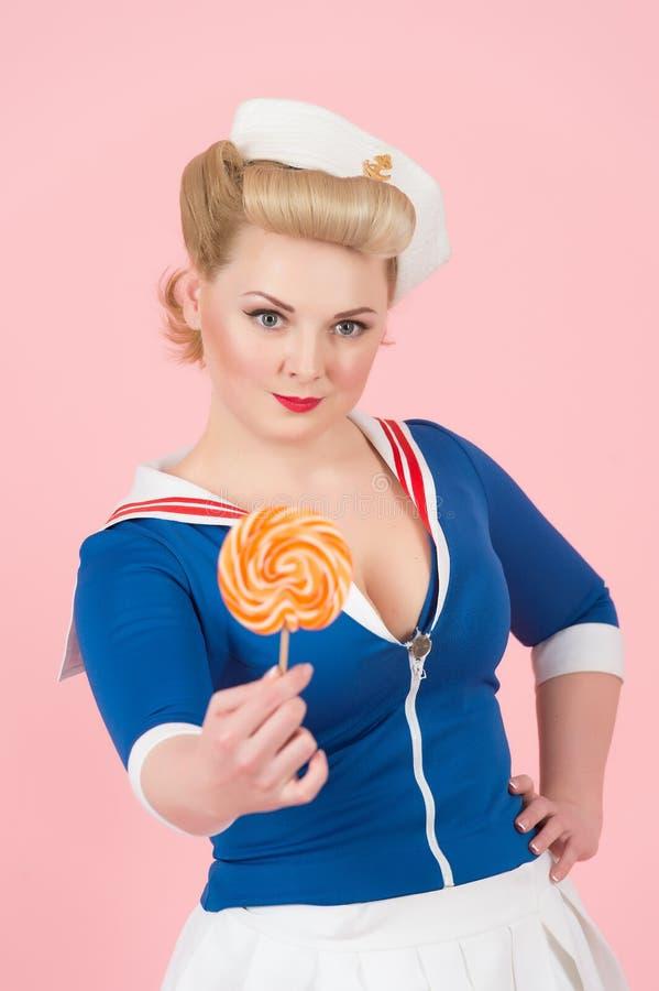 魅力有大棒棒糖的画报夫人 棒棒糖在手中减速火箭的被称呼的白肤金发的女孩 画报样式和糖果的白肤金发的妇女 免版税库存照片