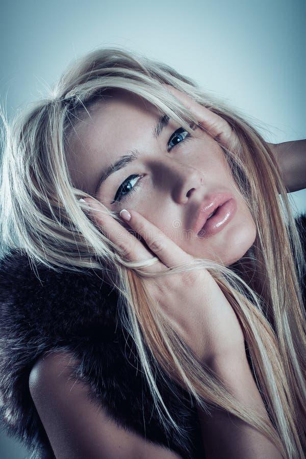 魅力美丽的白肤金发的少妇时尚画象毛皮的 免版税库存图片