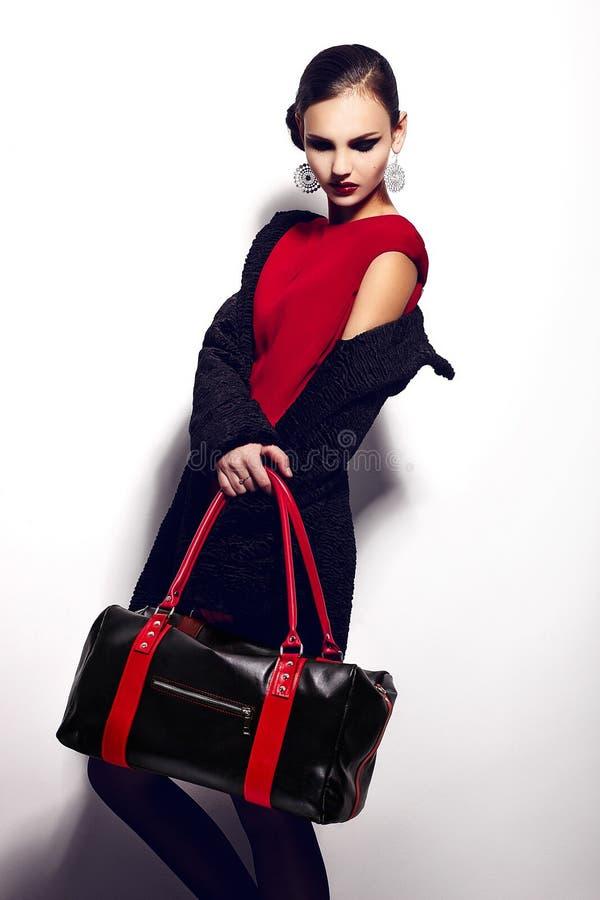魅力美好的性感的时髦的深色的白种人少妇模型特写镜头画象在红色礼服的有黑b的 库存照片