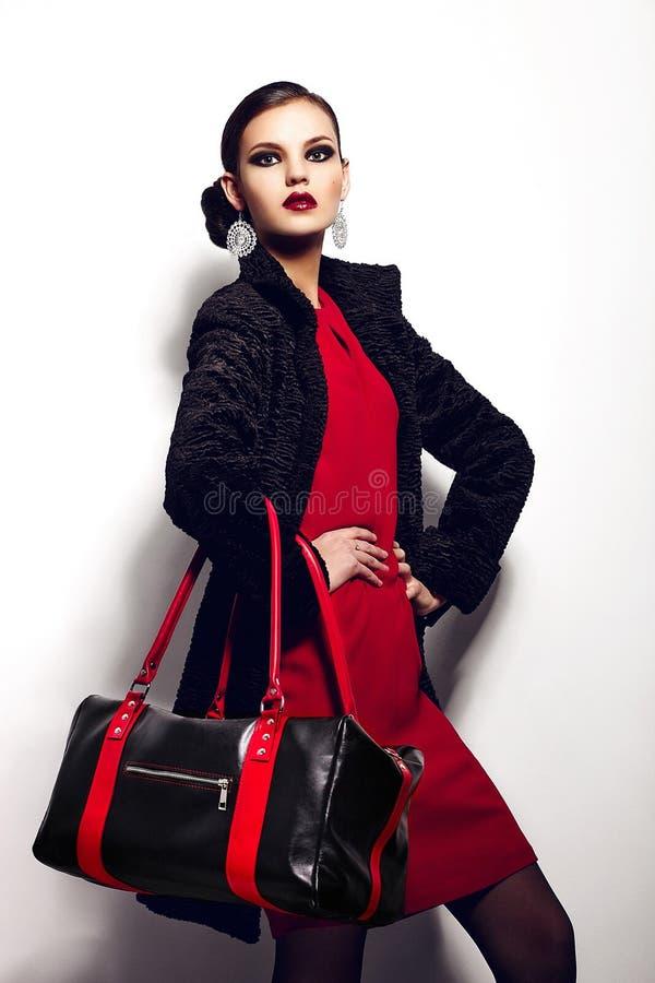魅力美好的性感的时髦的深色的白种人少妇模型特写镜头画象在红色礼服的有黑b的 库存图片
