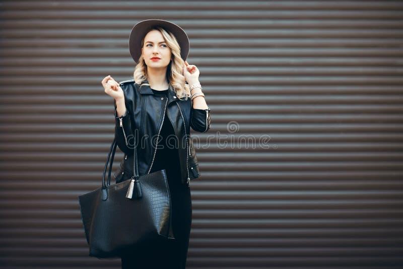 魅力肉欲的年轻时髦的夫人街道画象穿时髦秋天服装的 黑帽会议和皮革的白肤金发的妇女 免版税库存照片