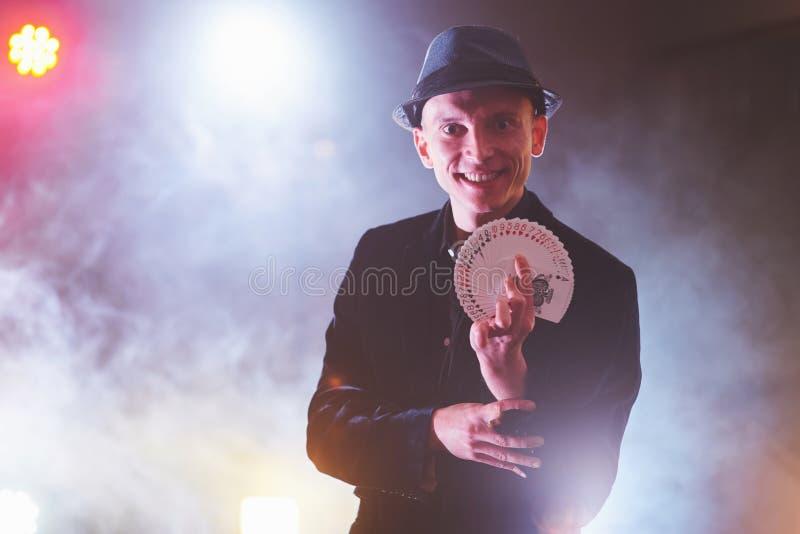 魔术师与纸牌的陈列把戏 魔术或手巧,马戏,赌博 变戏法的人在有雾的暗室 免版税库存图片