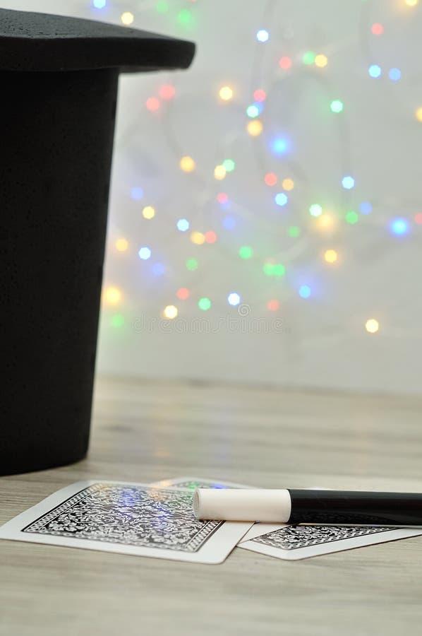 魔术师帽子、鞭子和卡片反对出于焦点光背景 库存照片
