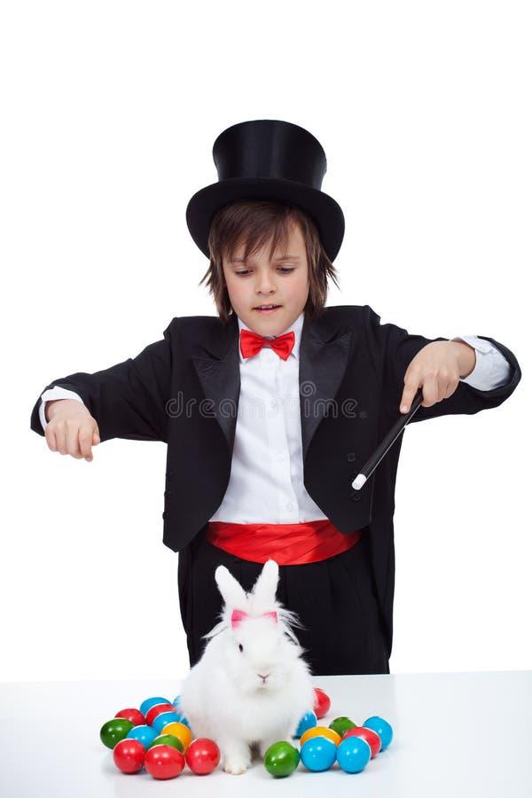 魔术师男孩执行一个魔术技巧与复活节兔子和一些五颜六色的鸡蛋 免版税库存照片