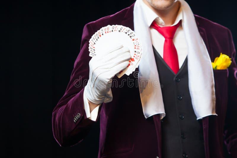 魔术师陈列的中央部位散开了卡片反对黑背景 魔术师,变戏法者人,滑稽的人,黑 库存照片