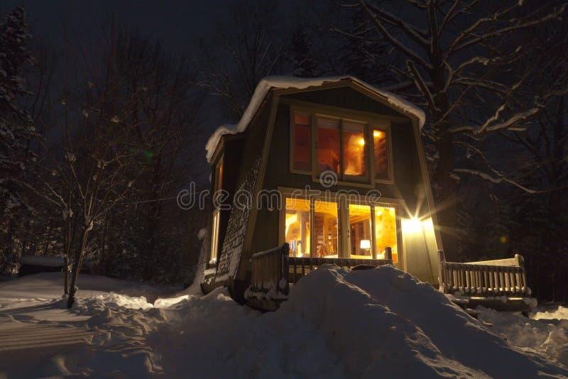 魔术晚上冬天 在森林掩藏的积雪的客舱 免版税库存图片