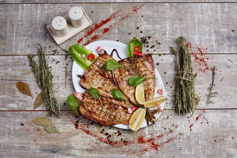 鱼在格栅烹调了在木背景的餐馆 库存图片