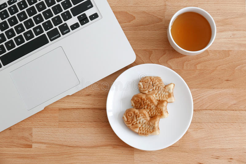 鱼塑造奶蛋烘饼用茶和膝上型计算机 图库摄影