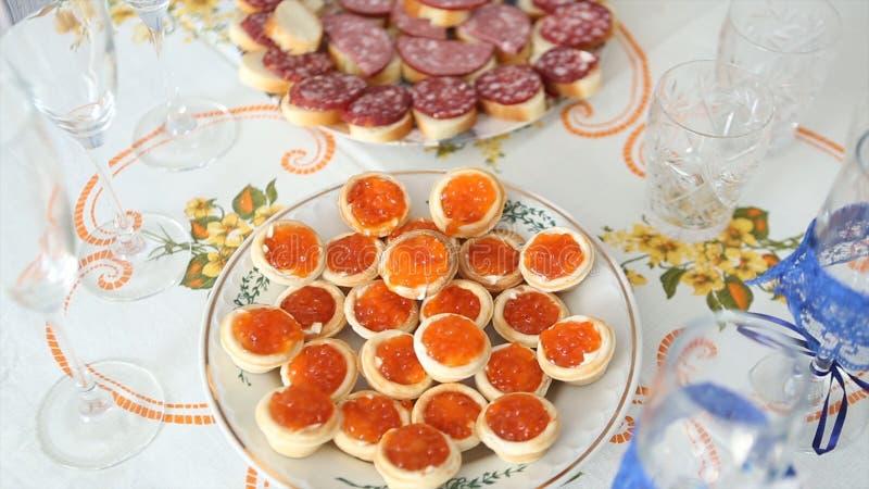 鱼子酱在豪华桌上的点心` 在桌上的红色鱼子酱和鱼草莓 婚姻 图库摄影