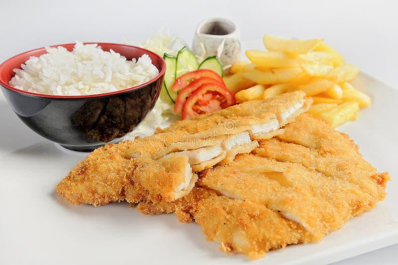 鱼宴-与菜的油煎的鳕鱼片 库存图片