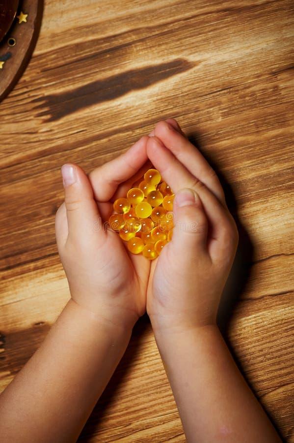 鱼油胶囊对于儿童` s handprints 关闭 营养和维生素 库存照片