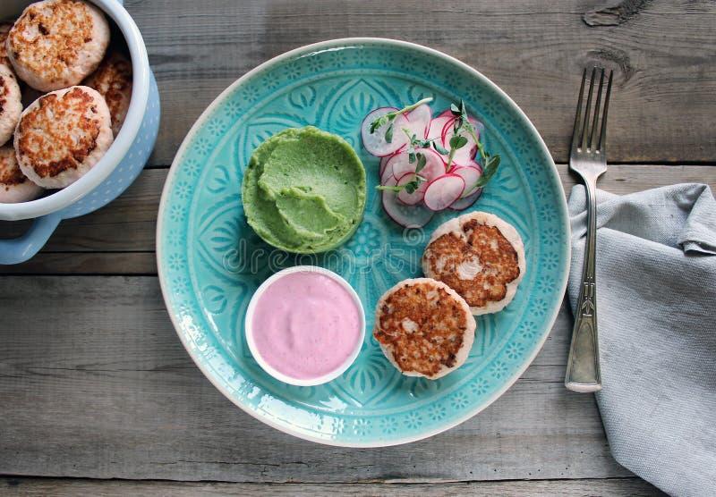 鱼炸肉排用绿色土豆泥 桃红色调味汁和萝卜和microgreens沙拉 西红柿汁 库存照片