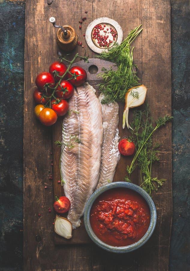 鱼烹调 两个绿鳕或coafish内圆角在黑暗变老了木背景用西红柿酱,新蕃茄束 免版税库存照片