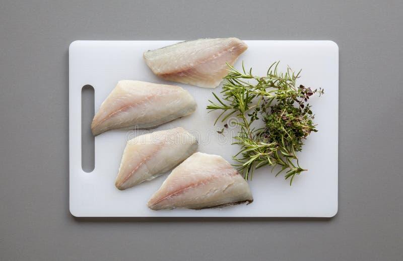 鱼用在砧板的草本 免版税库存图片