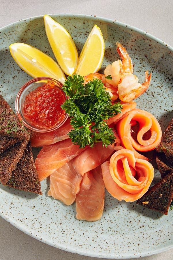 鱼盛肉盘用轻盐味的三文鱼,熏制鲑鱼,红色鱼子酱和博罗季诺黑面包多士 免版税库存图片