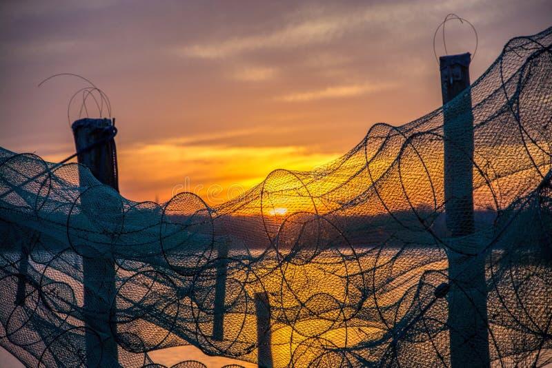鱼设陷井在日落 库存图片