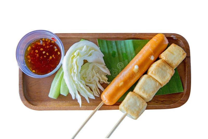 鱼豆腐和香肠在串有在木板材冲切在白色被隔绝的菜的 免版税库存图片