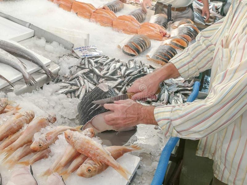 鱼贩子切开一条鱼在雅典主要市场上 库存照片