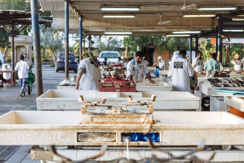 鱼贩子和海鲜卖主在半室外,露天海鲜市场上在棕榈Deira地铁车站附近在迪拜 图库摄影