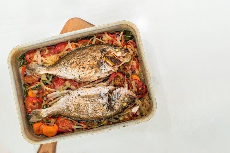 鱼,烹调在金属烘烤的盘子的菜坐垫在白色背景 库存图片