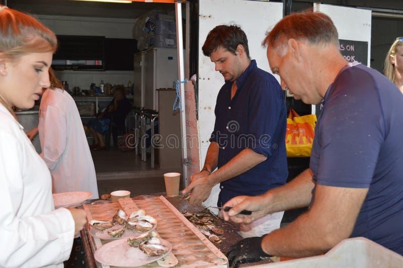 鱼贩子准备并且去外皮访客的牡蛎在Whitstable牡蛎节日 库存照片