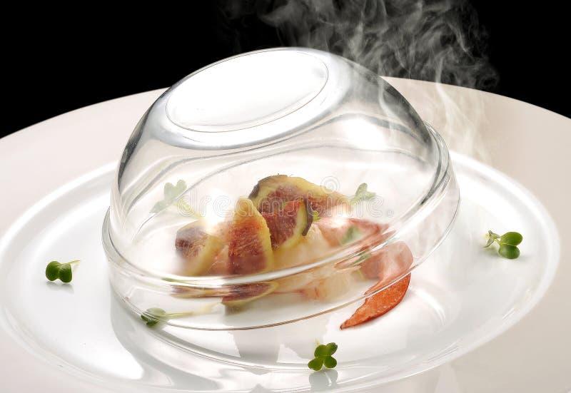 鱼宴,龙虾和无花果抽烟 库存图片