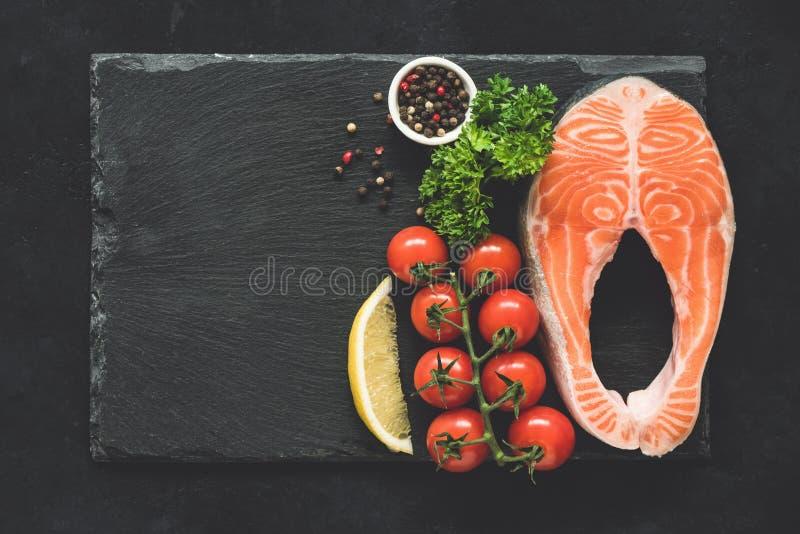 鲑鱼排和菜在黑板岩背景 免版税图库摄影