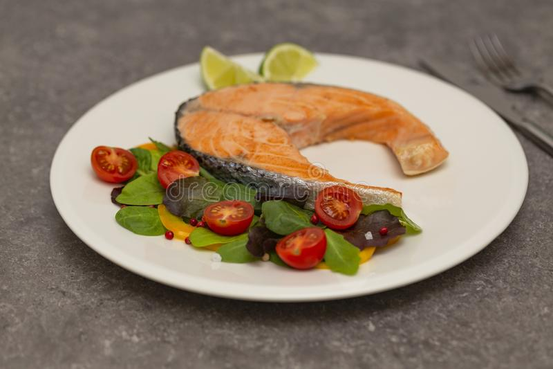 鲑鱼排晚餐用草本和蕃茄 免版税图库摄影